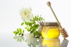 玻璃瓶子在白色背景的蜂蜜 库存照片