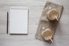 玻璃瓶子杯子充满香蕉,猕猴桃,苹果圆滑的人,顶上的看法 与铅笔的空白的笔记薄 r 库存照片