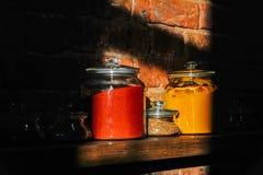 玻璃瓶子用在一个木架子的香料填装了 图库摄影