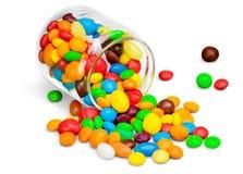 玻璃瓶子用在白色的五颜六色的糖果 免版税图库摄影