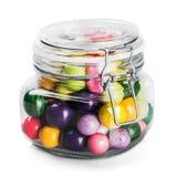玻璃瓶子用在白色隔绝的多彩多姿的糖果 免版税库存照片