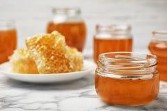 玻璃瓶子用甜蜂蜜 免版税库存照片