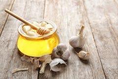 玻璃瓶子用蜂蜜和大蒜作为自然冷的补救 库存照片