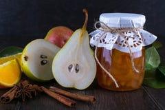 玻璃瓶子自创梨和橙色果酱用新鲜水果在桌上 免版税库存照片