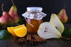 玻璃瓶子自创梨和橙色果酱用新鲜水果在桌上 免版税库存图片