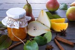 玻璃瓶子自创梨和橙色果酱用新鲜水果在桌上 图库摄影