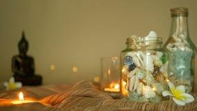 玻璃瓶用贝壳,珊瑚,与蜡烛光,羽毛花的海洋项目填装了,坐装饰的菩萨 股票视频