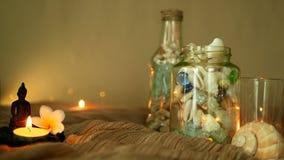 玻璃瓶用贝壳,珊瑚,与蜡烛光,羽毛花的海洋项目填装了,坐装饰的菩萨 股票录像
