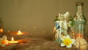 玻璃瓶用贝壳,珊瑚,与蜡烛光,羽毛装饰的赤素馨花花的海洋项目填装了 股票录像