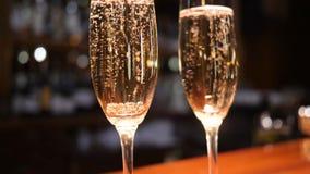 玻璃用与上升在未聚焦的背景的泡影的香槟