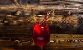 玻璃用倾吐与液体的酒与飞溅并且滴水 刷新的饮料概念 填装与的葡萄酒杯 库存图片