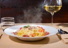 玻璃用在意粉面团用虾,搓碎干酪附近的酒 免版税库存图片
