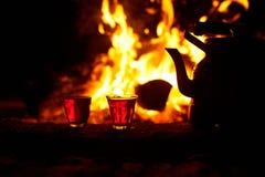 玻璃用在火附近的茶与火焰状木头在晚上 免版税库存图片