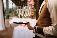 玻璃用在盘子的香槟 遇见客人 免版税库存图片