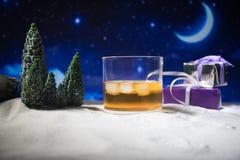 玻璃用在雪的威士忌酒与艺术品圣诞装饰 杯在白雪的威士忌酒有美好的假日背景 免版税图库摄影