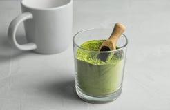 玻璃用搽粉的matcha茶和瓢 免版税图库摄影