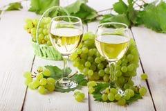 玻璃用白葡萄酒和新鲜的葡萄在一张木桌上 免版税图库摄影