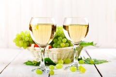 玻璃用白葡萄酒和新鲜的葡萄在一张木桌上 免版税库存照片