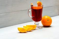 玻璃用被仔细考虑的酒或热的萍果汁在水多的橙色果子附近在白色木背景 饮料或饮料用桔子 免版税库存照片