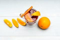 玻璃用被仔细考虑的酒或热的萍果汁在水多的橙色果子附近在白色背景 饮料或饮料用桔子和 免版税图库摄影