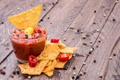 玻璃用辣调味汁调味汁和烤干酪辣味玉米片 免版税库存图片
