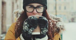玻璃的一个女孩在城市附近走并且喝热的咖啡 一名微笑的妇女喝奶昔,当走时 股票视频