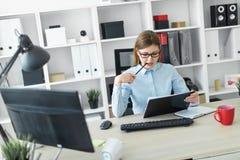 玻璃的一个女孩在她的手上坐在一张桌上在办公室,拿着一支铅笔并且与文件一起使用 免版税库存图片