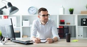 玻璃的一个年轻人在一张桌附近在他的手上站立在办公室并且拿着一支铅笔 库存照片