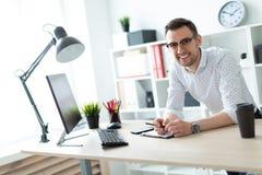 玻璃的一个年轻人在一张桌附近在他的手上站立在办公室并且拿着一支铅笔 库存图片