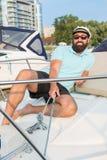 玻璃的一个年轻人坐拉扯绞盘的游艇 库存照片