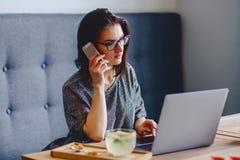 玻璃的一个美丽的女孩由一台膝上型计算机的电话讲话在加州 免版税库存照片