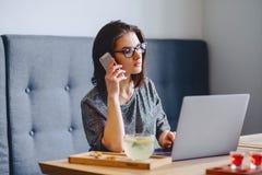 玻璃的一个美丽的女孩由一台膝上型计算机的电话讲话在加州 图库摄影