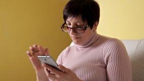 玻璃的一名妇女写消息的在她全新的智能手机,当在家时坐有一个白色枕头的长沙发 股票视频