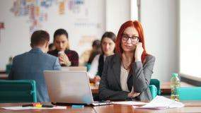 玻璃的一名姜妇女坐在办公室由膝上型计算机和谈话在她的电话 股票视频