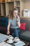玻璃的一名年轻女实业家在她的手机坐在旅馆大厅饮用的咖啡的一个沙发并且谈话 库存图片