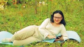 玻璃的一名年轻快乐的妇女在森林在瑜伽的一个地毯在片剂的一个信使说谎并且沟通 影视素材