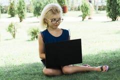 玻璃的一美女在估计工作,外面 学生在膝上型计算机做教训 图库摄影