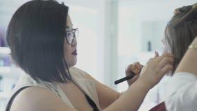 玻璃的亚裔化妆师在模型上把构成刷子放在沙龙 影视素材