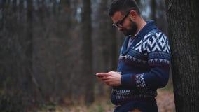 玻璃的人通过秋天森林走并且使用智能手机 股票视频