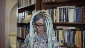 玻璃的俏丽的行家妇女与选择读的dreadlocks书准时悠闲时间在大学图书馆 股票录像