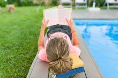 玻璃的十几岁的女孩读一本书,背景游泳池,在房子附近的草坪 学校,教育,知识,青少年 免版税图库摄影