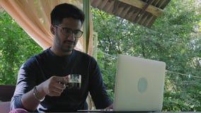 玻璃的印度人喝从玻璃杯的浓咖啡和神色在膝上型计算机显示器,坐在表上在公园 影视素材