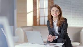 玻璃的可爱的夫人微笑入照相机,聪明和负责任的雇员的 免版税图库摄影