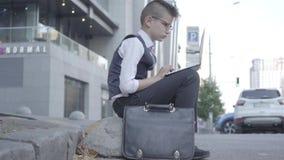 玻璃的可爱的穿着体面的男孩坐在膝上型计算机特写镜头的街道工作 行动象成人的严肃的孩子 影视素材