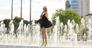 玻璃的夏天女孩临近喷泉 库存照片