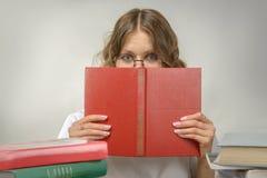 玻璃的女孩与一本红色书 免版税库存照片