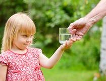 玻璃的女孩少许采取的水 库存照片