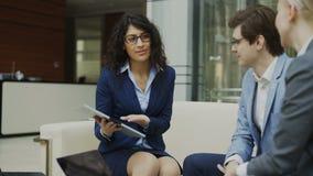 玻璃的女实业家谈和duscussing同商务伙伴的期货合约坐长沙发在现代办公室 股票录像