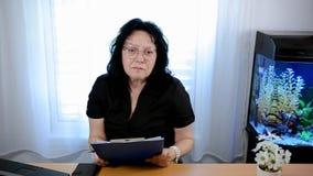 玻璃的女性心理学家认真听某人和采取笔记 股票录像