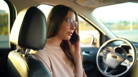 玻璃的妇女发表演讲关于智能手机并且喝在汽车的咖啡 股票视频